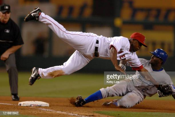 Joey Gathright of the Kansas City Royals slides beneath the tag of a diving Chone Figgins of the Los Angeles Angels of Anaheim during Major League...