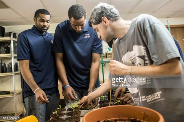 Joey Gidargidz shows Chase Tapley and Ron Anderson of the Tulsa 66ers how to transfer plants to new pots during the NBA DLeague community relations...