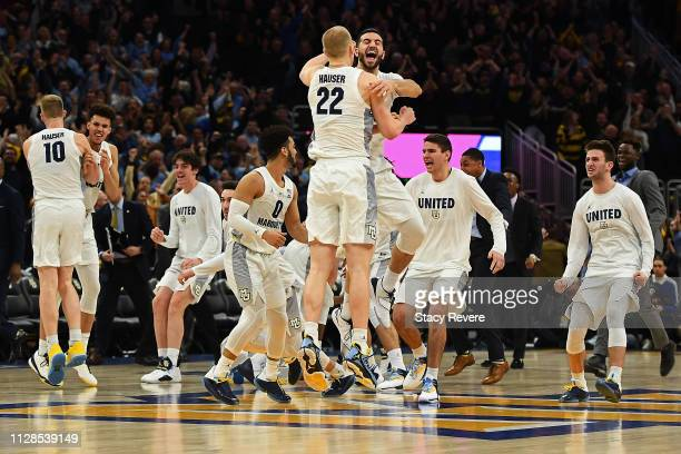 Joey Hauser and Joseph Chartouny of the Marquette Golden Eagles celebrate a victory over the Villanova Wildcats at Fiserv Forum on February 09, 2019...
