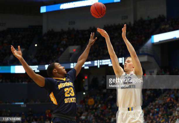 Joey Hauser of the Marquette Golden Eagles takes a shot over KJ Williams of the Murray State Racers during the first round game of the 2019 NCAA...