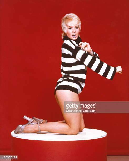 Joey Heatherton US actress dancer and singer poses wearing a top with blackandwhite horizontal stripes while kneeling on a podium in a studio...