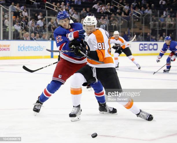 Joey Keane of the New York Rangers holds on to Carsen Twarynski of the Philadelphia Flyers during the first period at Madison Square Garden on...