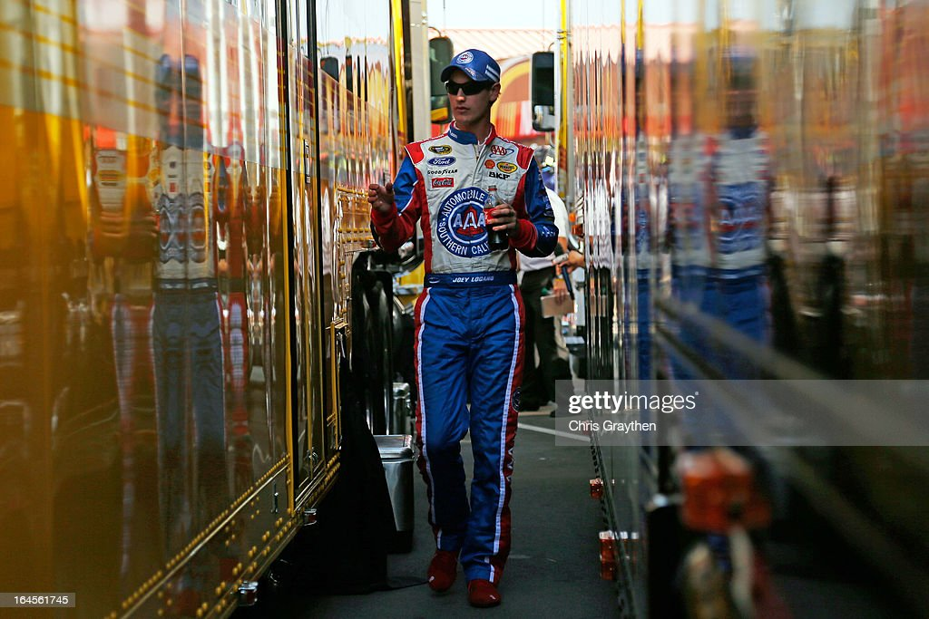 Joey Logano, driver of the #22 AAA Southern California Ford, walks back to his hauler in the garage area after an incident with Denny Hamlin (not pictured), driver of the #11 FedEx Express Toyota, in the last lap of the NASCAR Sprint Cup Series Auto Club 400 at Auto Club Speedway on March 24, 2013 in Fontana, California.
