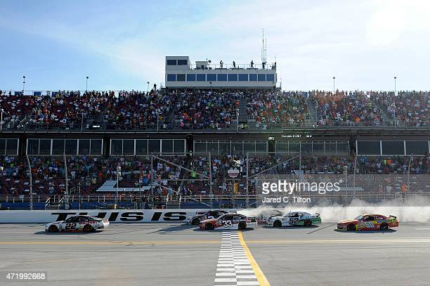 Joey Logano driver of the Discount Tire Ford takes the checkered flag to win the NASCAR XFINITY Series Winn Dixie 300 at Talladega Superspeedway on...