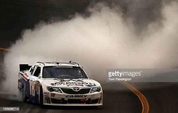 Joey Logano driver of the GameStop/Epic Mickey2 Toyota celebrates with a burnout after winning the NASCAR Nationwide Series Great Clips 200 at...