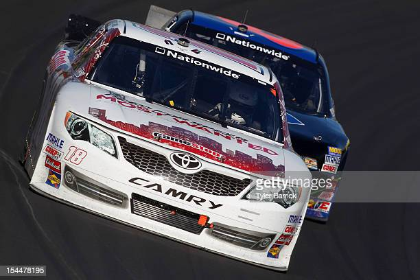 Joey Logano driver of the GameStop/Need For Speed Most Wanted Toyota leads Ricky Stenhouse Jr driver of the Cargill/Sam's Club Ford during the NASCAR...