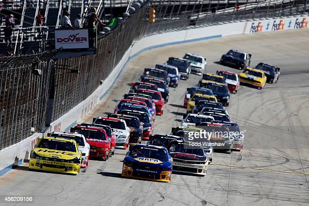 Joey Logano driver of the Hertz Ford and Chase Elliott driver of the NAPA Auto Parts Chevrolet lead the field to the green flag to start the NASCAR...