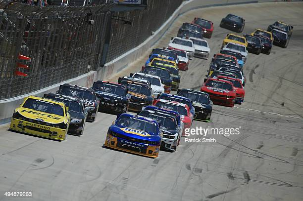 Joey Logano driver of the Hertz Ford and Chase Elliott driver of the NAPA Auto Parts Chevrolet lead the field at the start of the NASCAR Nationwide...