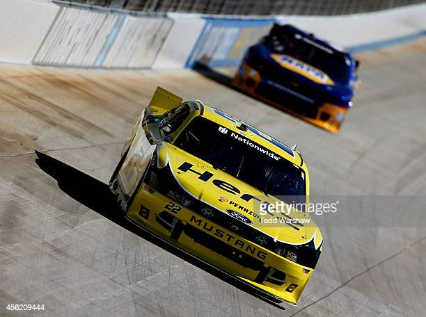 Joey Logano driver of the Hertz Ford leads Chase Elliott driver of the NAPA Auto Parts Chevrolet during the NASCAR Nationwide Series Dover 200 at...