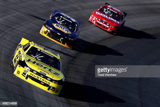 Joey Logano driver of the Hertz Ford leads Chase Elliott driver of the NAPA Auto Parts Chevrolet and Chris Buescher driver of the Roush Performance...