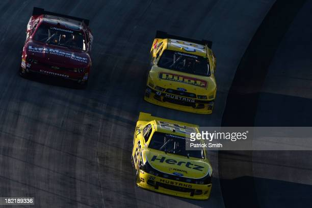 Joey Logano driver of the Hertz Ford leads Michael Annett driver of the Pilot Travel Centers Ford and Kyle Larson driver of the LiftMaster Chevrolet...