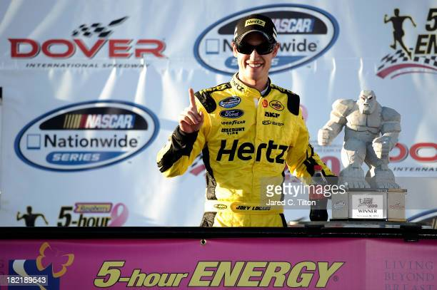 Joey Logano driver of the Hertz Ford poses with the Miles the Monster trophy after winning the NASCAR Nationwide Series 5Hour Energy 200 Benefiting...