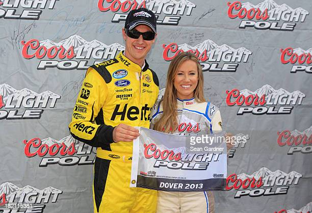 Joey Logano driver of the Hertz Fordand Miss Coors Light Rachel Rupert pose with the Coors Light Pole Award after Logano qualified for the pole for...
