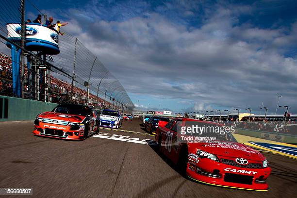 Joey Logano, driver of the Home Depot/redbeacon.com Toyota, and Marcos Ambrose, driver of the Black & Decker Ford, lead the field during the...