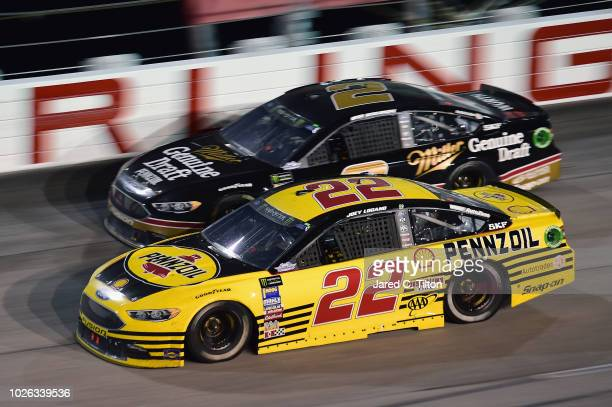 Joey Logano driver of the Pennzoil Ford races Brad Keselowski driver of the Miller Genuine Draft Ford during the Monster Energy NASCAR Cup Series...