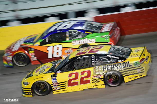 Joey Logano driver of the Pennzoil Ford races Kyle Busch driver of the Skittles 1998 Retro Toyota during the Monster Energy NASCAR Cup Series...