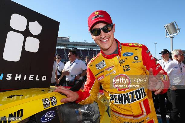 Joey Logano, driver of the Shell Pennzoil Ford, affixes the winners decal after winning the NASCAR Cup Series FanShield 500 at Phoenix Raceway on...