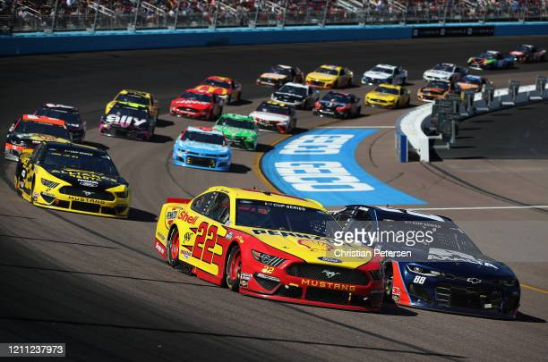 Joey Logano, driver of the Shell Pennzoil Ford, and Alex Bowman, driver of the Axalta Chevrolet, lead during the NASCAR Cup Series FanShield 500 at...