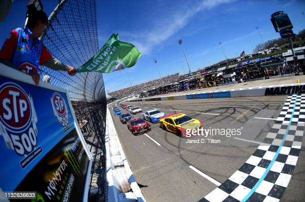 Joey Logano driver of the Shell Pennzoil Ford and Aric Almirola driver of the SHAZAMSmithfield Ford lead the field to the green flag to start the...