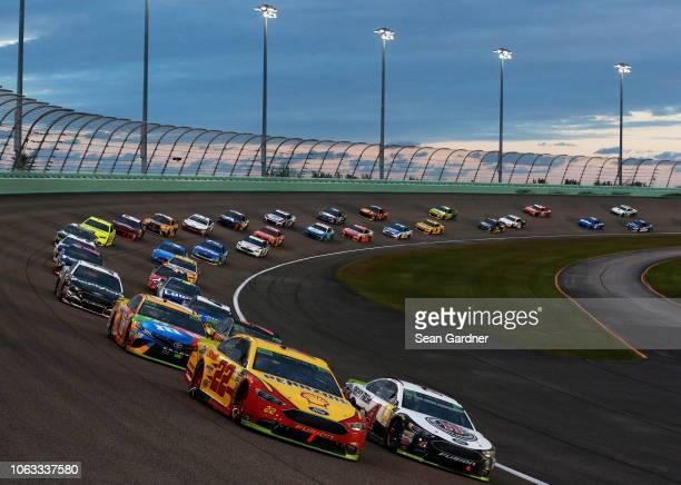 Joey Logano driver of the Shell Pennzoil Ford and Kevin Harvick driver of the Jimmy John's Ford lead a pack of cars during the Monster Energy NASCAR...