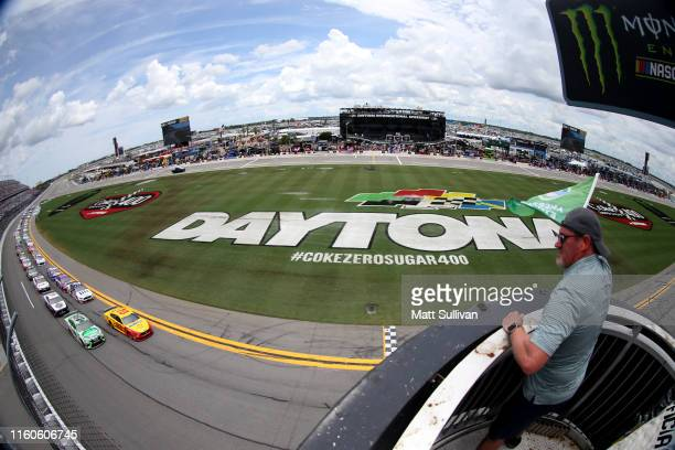 Joey Logano driver of the Shell Pennzoil Ford and Kyle Busch driver of the Interstate Batteries Toyota lead the field to the green flag to start the...