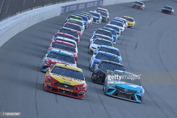 Joey Logano driver of the Shell Pennzoil Ford and Martin Truex Jr driver of the AutoOwners Insurance Toyota lead the field to a restart during the...
