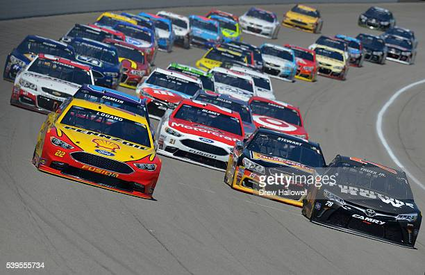Joey Logano driver of the Shell Pennzoil Ford and Martin Truex Jr driver of the Furniture Row Toyota lead the field during the NASCAR Sprint Cup...