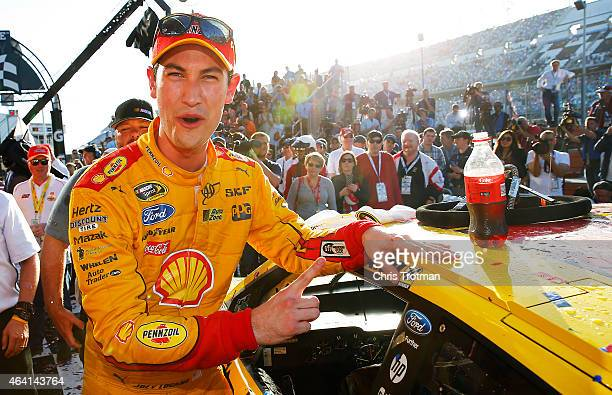 Joey Logano driver of the Shell Pennzoil Ford applies the winner's decal in Victory Lane after winning the NASCAR Sprint Cup Series 57th Annual...
