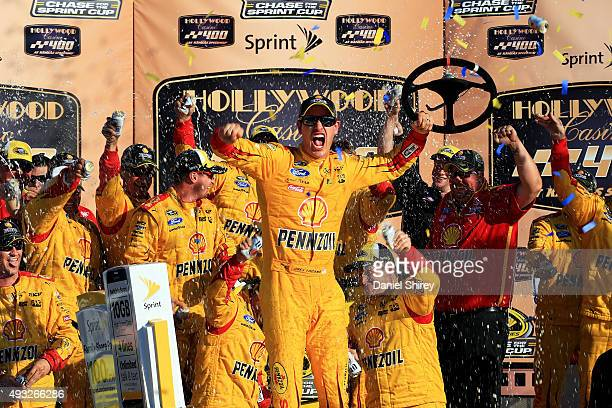 Joey Logano driver of the Shell Pennzoil Ford celebrates in Victory Lane after winning the NASCAR Sprint Cup Series Hollywood Casino 400 at Kansas...