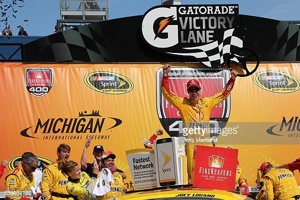 Joey Logano driver of the Shell Pennzoil Ford celebrates in victory lane after winning the NASCAR Sprint Cup Series FireKeepers Casino 400 at...