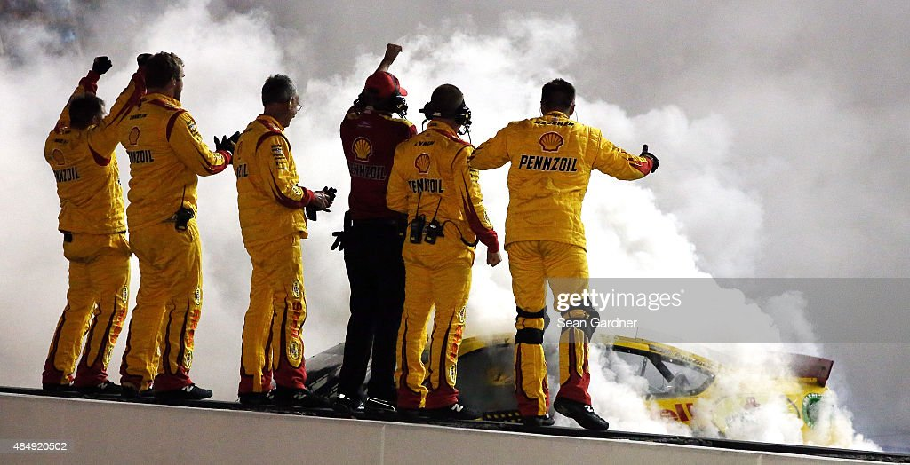 Joey Logano, driver of the #22 Shell Pennzoil Ford, celebrates with a burnout as his crew members react after winning the NASCAR Sprint Cup Series IRWIN Tools Night Race at Bristol Motor Speedway on August 22, 2015 in Bristol, Tennessee.