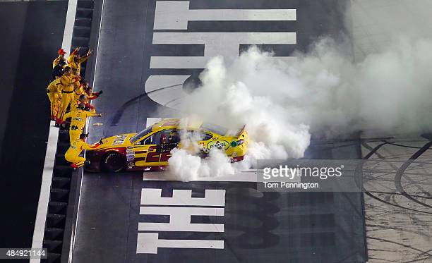 Joey Logano driver of the Shell Pennzoil Ford celebrates with a burnout as his crew members react after winning the NASCAR Sprint Cup Series IRWIN...