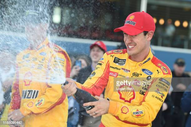 Joey Logano driver of the Shell Pennzoil Ford celebrates with a burnout after winning the Monster Energy NASCAR Cup Series FireKeepers Casino 400 at...