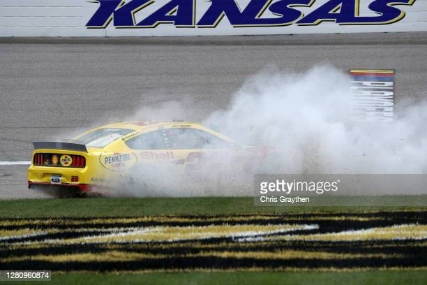 Joey Logano, driver of the Shell Pennzoil Ford, celebrates with a burnout after winning the NASCAR Cup Series Hollywood Casino 400 at Kansas Speedway...