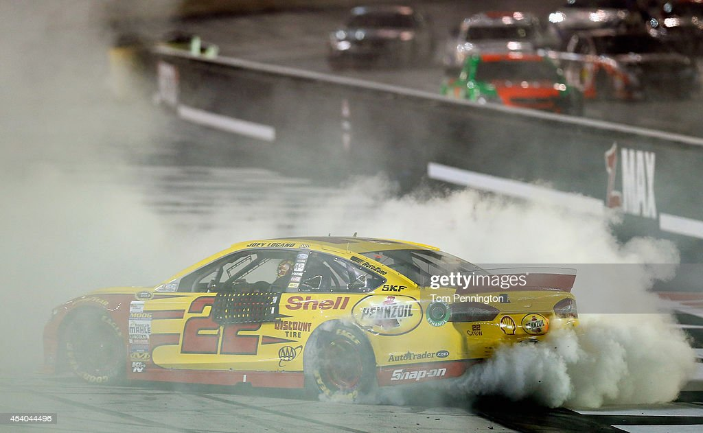 Joey Logano, driver of the #22 Shell Pennzoil Ford, celebrates with a burnout after winning the NASCAR Sprint Cup Series Irwin Tools Night Race at Bristol Motor Speedway on August 23, 2014 in Bristol, Tennessee.