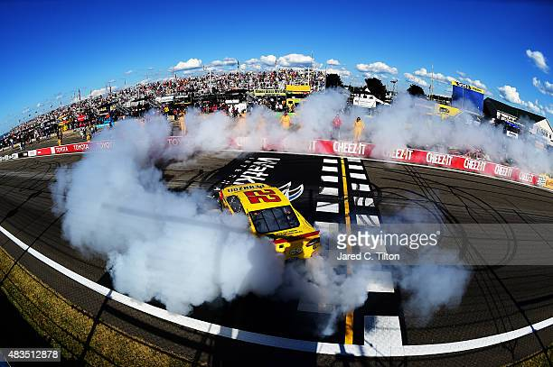 Joey Logano driver of the Shell Pennzoil Ford celebrates with a burnout after winning the NASCAR Sprint Cup Series CheezIt 355 at the Glen at Watkins...