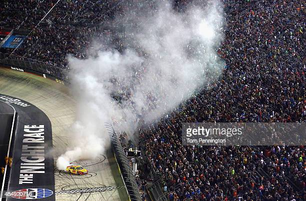 Joey Logano driver of the Shell Pennzoil Ford celebrates with a burnout after winning the NASCAR Sprint Cup Series IRWIN Tools Night Race at Bristol...