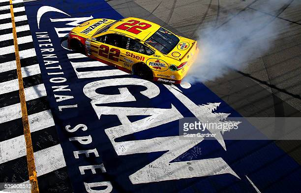 Joey Logano driver of the Shell Pennzoil Ford celebrates with a burnout after winning the NASCAR Sprint Cup Series FireKeepers Casino 400 at Michigan...