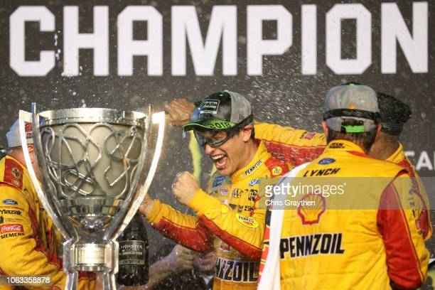 Joey Logano, driver of the Shell Pennzoil Ford, celebrates with crew members in Victory Lane after winning the Monster Energy NASCAR Cup Series Ford...
