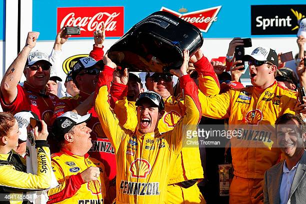 Joey Logano, driver of the Shell Pennzoil Ford, celebrates with the The Harley J. Earl Trophy in Victory Lane after winning the NASCAR Sprint Cup...