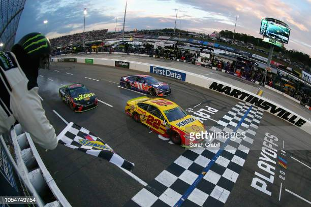 Joey Logano driver of the Shell Pennzoil Ford crosses the finish line ahead of Martin Truex Jr driver of the 5hour ENERGY/Bass Pro Shops Toyota to...
