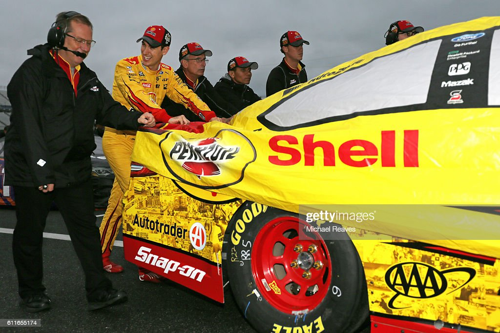 Joey Logano, driver of the #22 Shell Pennzoil Ford, helps to push his car to the garage after qualifying for the NASCAR Sprint Cup Series Citizen Solider 400 was cancelled at Dover International Speedway on September 30, 2016 in Dover, Delaware.