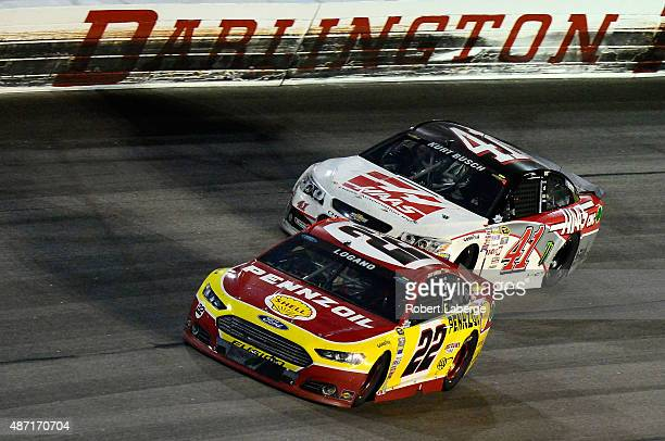 Joey Logano driver of the Shell Pennzoil Ford leads Kurt Busch driver of the Haas Automation Chevrolet during the NASCAR Sprint Cup Series Bojangles'...