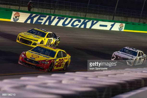 Joey Logano driver of the Shell Pennzoil Ford leads Landon Cassill driver of the StarCom Fiber Chevrolet and Erik Jones driver of the Freightliner...