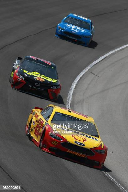 Joey Logano driver of the Shell Pennzoil Ford leads Martin Truex Jr driver of the 5hour ENERGY/Bass Pro Shops Chevrolet and Ryan Blaney driver of the...