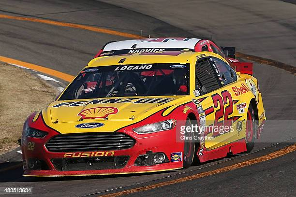 Joey Logano driver of the Shell Pennzoil Ford passes Kevin Harvick driver of the Budweiser/Jimmy John's Chevrolet on the final lap to win the NASCAR...