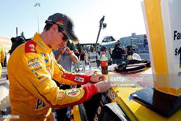 Joey Logano, driver of the Shell Pennzoil Ford, places the winner's decal on his car after winning the NASCAR Sprint Cup Series Hollywood Casino 400...