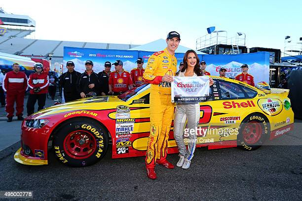 Joey Logano driver of the Shell Pennzoil Ford poses with Miss Coors Light Amanda Mertz and the Coors Light Pole award after qualifying for pole...