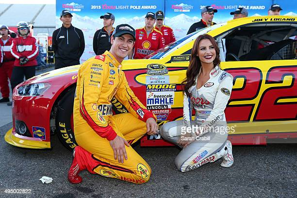 Joey Logano driver of the Shell Pennzoil Ford poses with Miss Coors Light Amanda Mertz as they affix the Coors Light Pole award decal after...