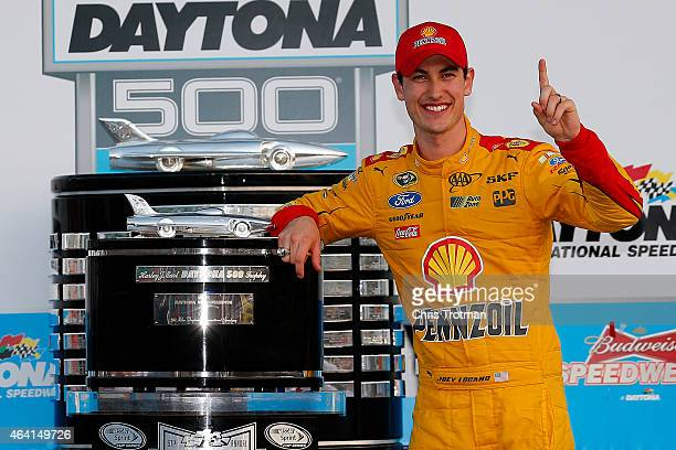 Joey Logano driver of the Shell Pennzoil Ford poses with the The Harley J Earl Trophy in Victory Lane after winning the NASCAR Sprint Cup Series 57th...